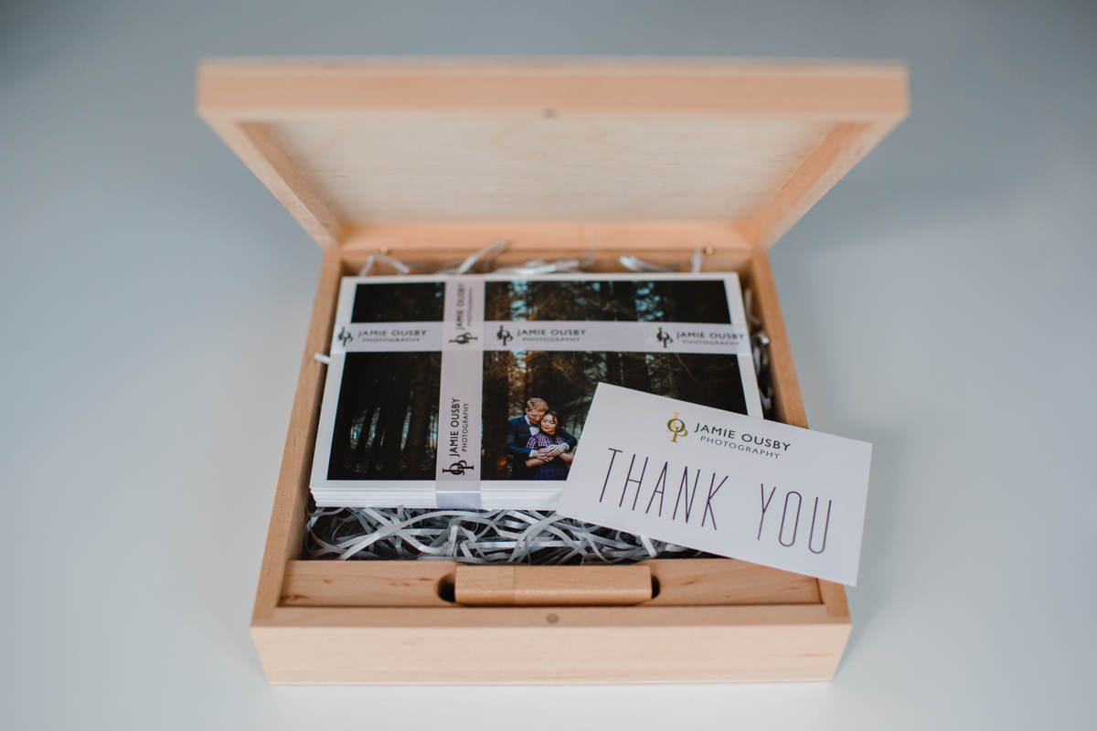 A wooden presentation box USB and prints on a table